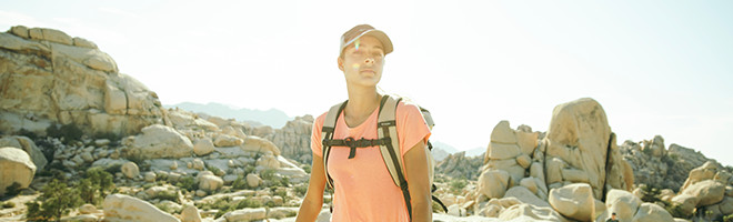 A woman wearing a hat and a backpack hiking in the desert.