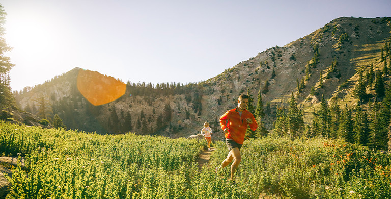 A man and a woman are trail-running through a mountain meadow on a sunny day.