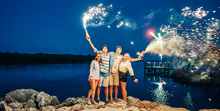 A group of friends enjoying fireworks by the harbor