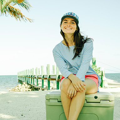 A female traveler sitting on a cooler on the beach.