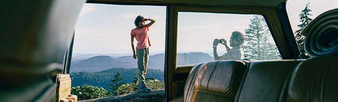 A man taking a photo of a woman at a scenic overlook.