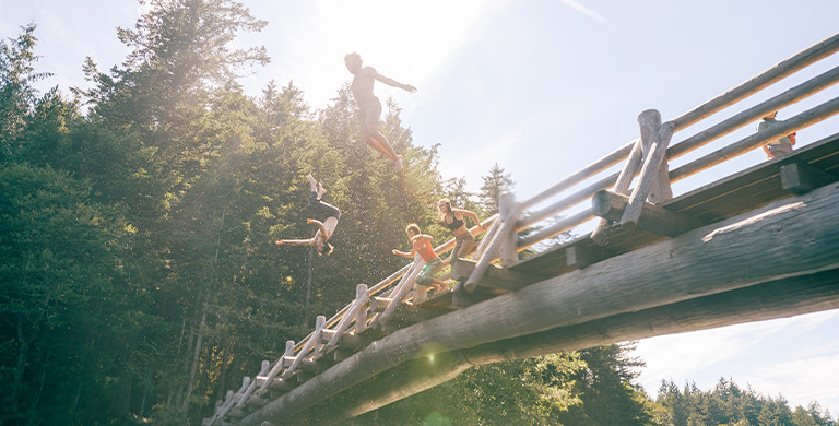 Four people in casual wear jump from a wooden footbridge into a river on a sunny day.