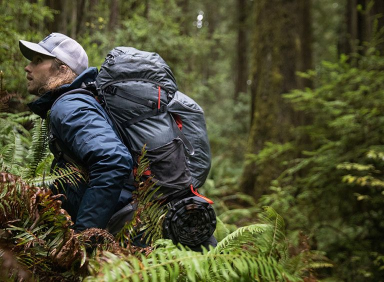 A man hiking in the forest wearing an Ozonic pack.