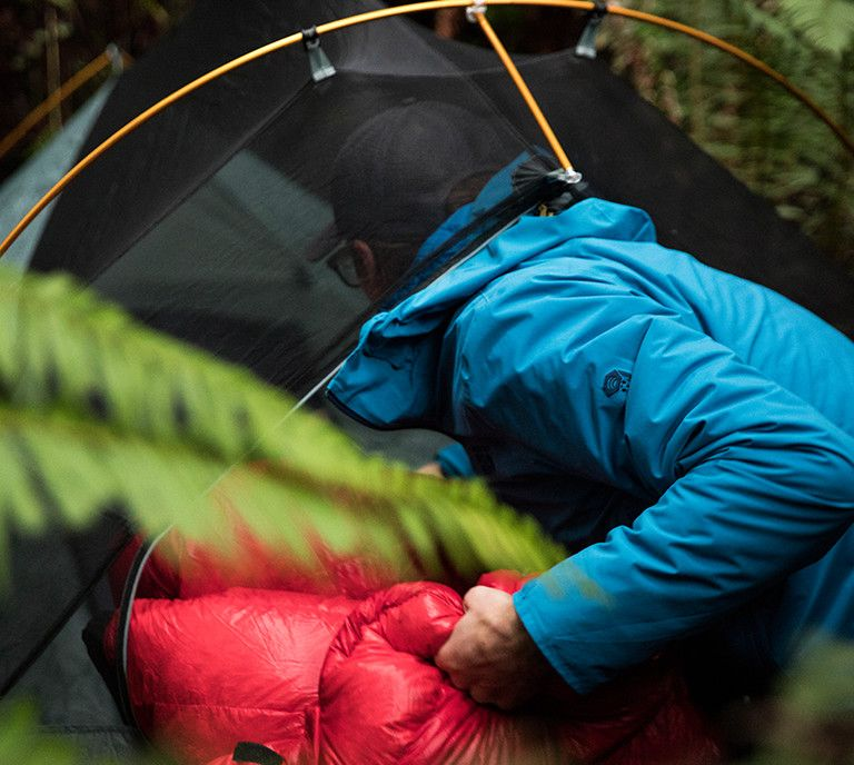 Man wearing Stretch Ozonic jacket getting in to a tent.