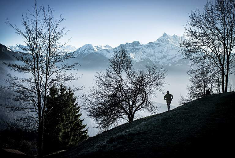 A trail runner runs along a hillside with a foggy valley below and snow-capped peaks in the distance.