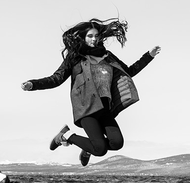 black and white image of a girl jumping in a jacket