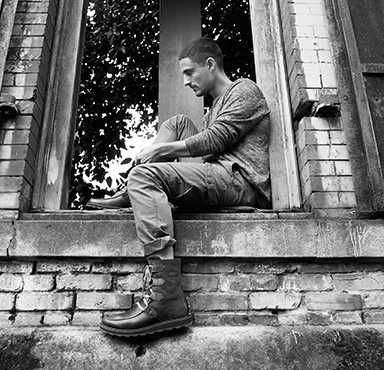 Black and white image of guy sitting on window sill wearing boots.