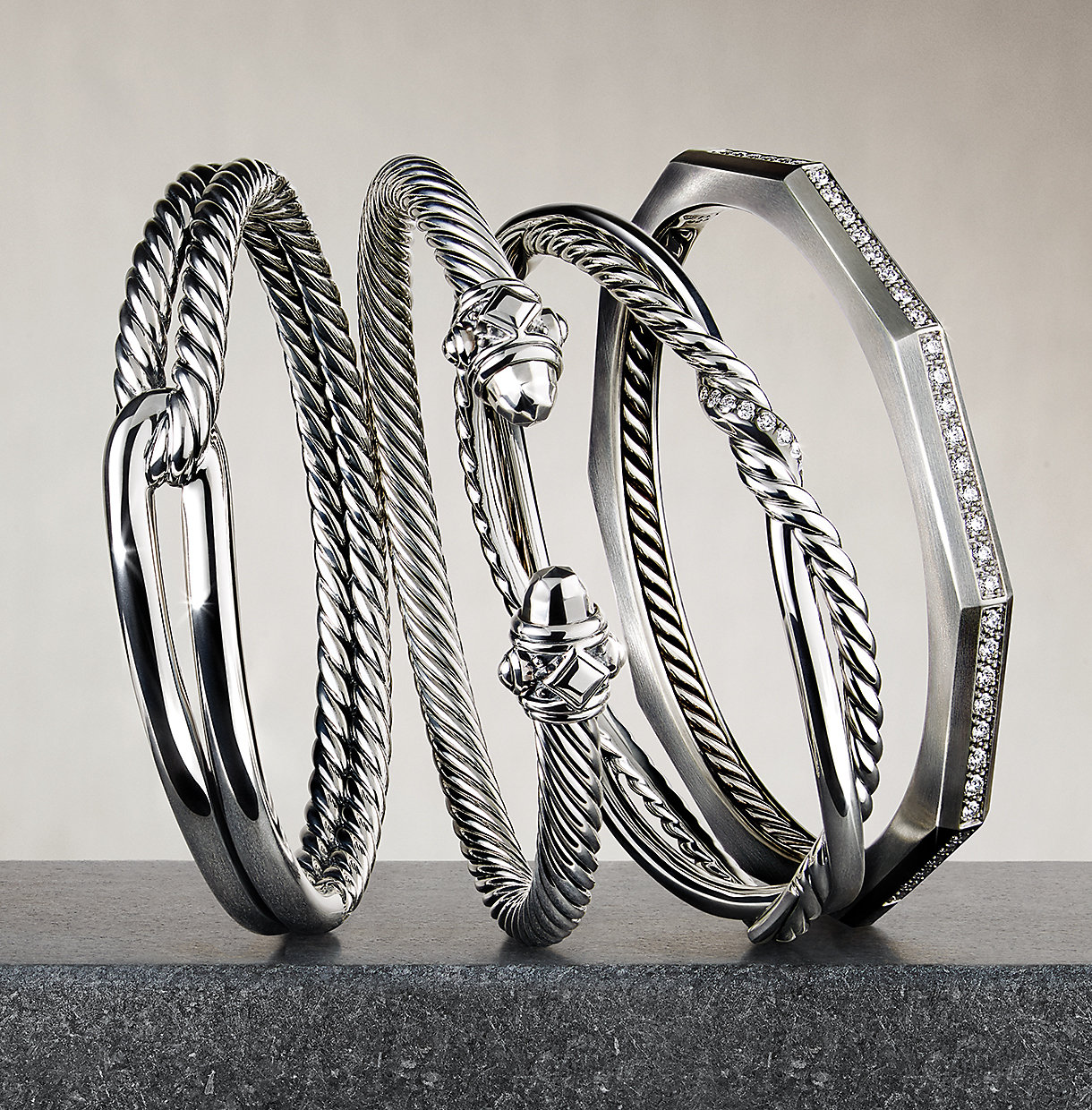 A stack of sterling silver and diamond bracelets