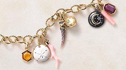 椭圆链黄金手链,饰有多个彩色护身符,置于一块石头上。