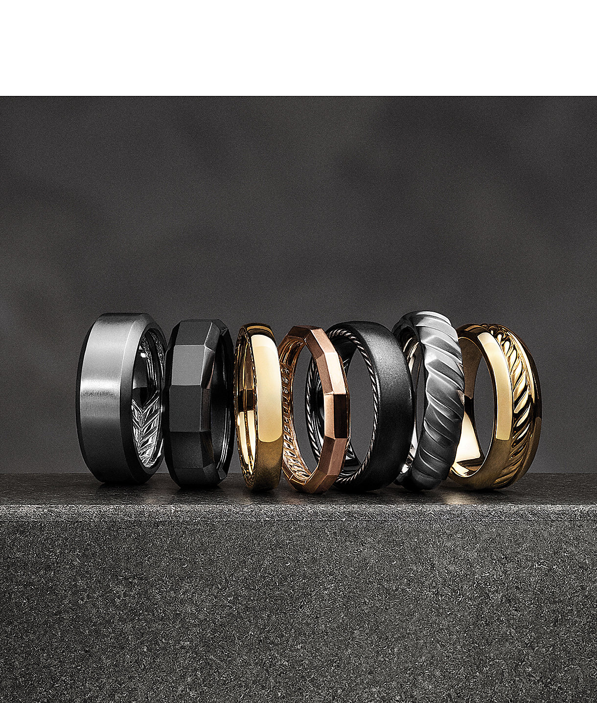 A row of men's bands in 18k yellow gold, titanium and sterling silver
