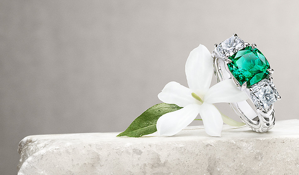 An engagement ring in platinum with diamonds and an emerald on a stone with jasmine flowers.