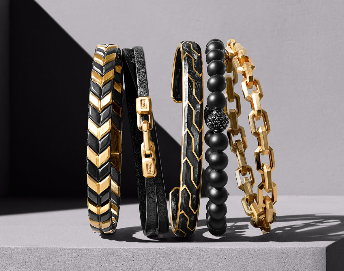 A color photo shows a horizontal stack of five David Yurman men's bracelets standing upright in front of a beige stone background partially covered with a diagonal shadow and on top of a beige stone surface, casting long shadows. From left is a Chevron design in 18K yellow gold and black titanium, a Streamline design in black leather and 18K yellow gold, a Forged Carbon design in 18K yellow gold, a Spiritual Beads design in black onyx with sterling silver and pavé black diamonds and a Streamline design in 18K yellow gold.