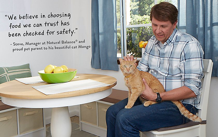 Man in chair petting cat - We believe in choosing food we can trust has been checked for safety.