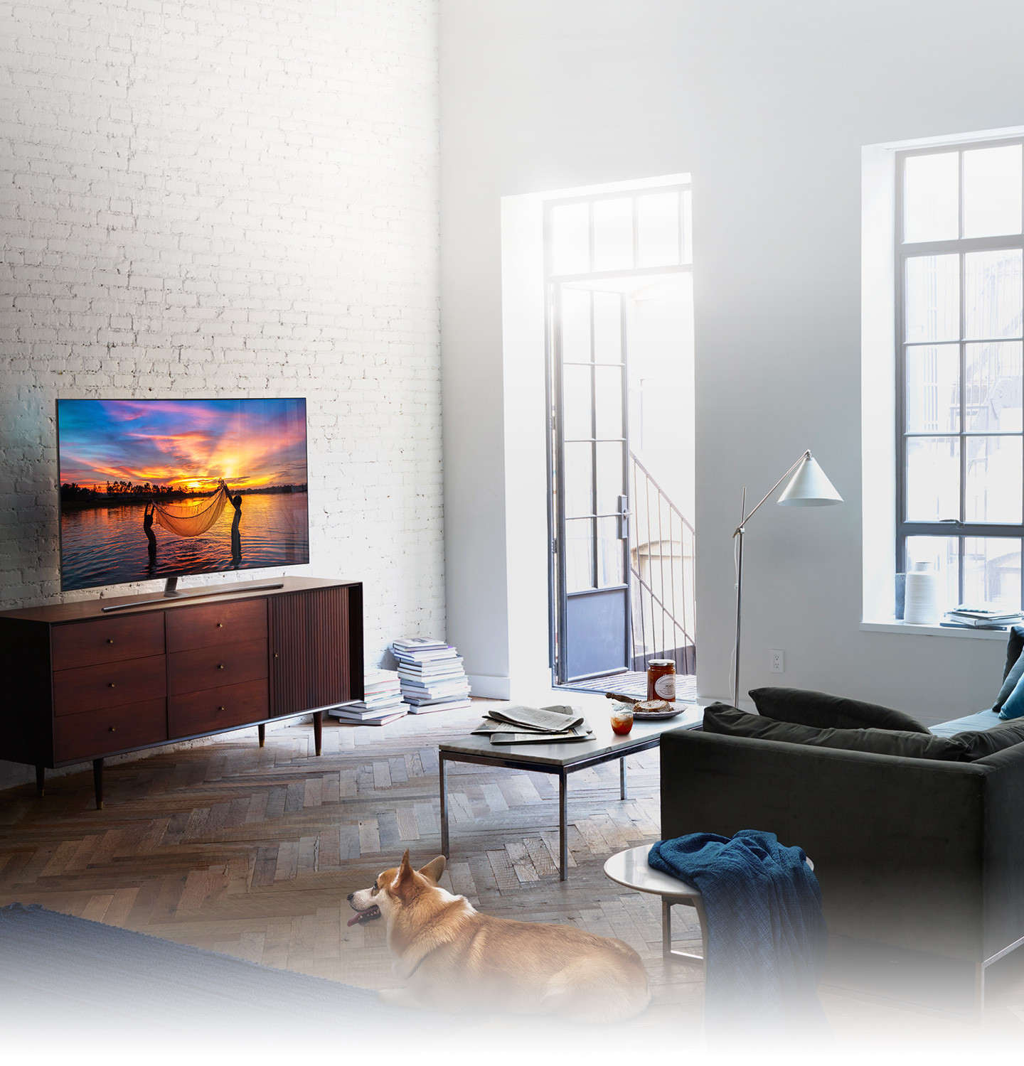 QLED TV has been set in the living room where the morning sun shines brightly and on its display shows children fishing with their net in the seashore glowing with the setting sun..