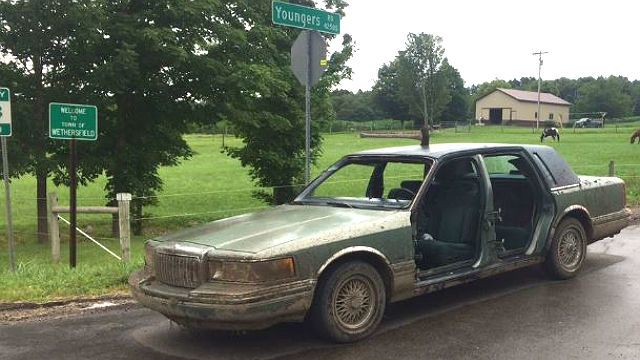 Man arrested after driving with ax in roof
