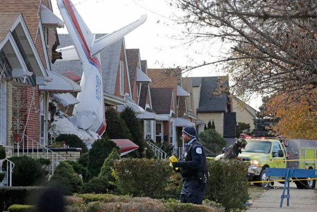 Police and fire officials walk near a small twin-engine cargo plane that crashed into a home on Chicago's southwest side early Tuesday, Nov. 18, 2014. The Aero Commander 500 that had taken off from Midway International Airport slammed into the front of the home and plunged into the basement. Fire Department spokesman Larry Langford says two occupants of the home were unhurt. The pilot was killed in the crash.