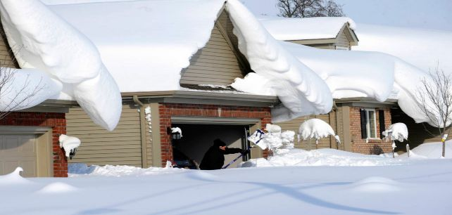 Snowdrifts create a beautiful setting as a man tries to dig out his driveway on Bowen Rd in Lancaste