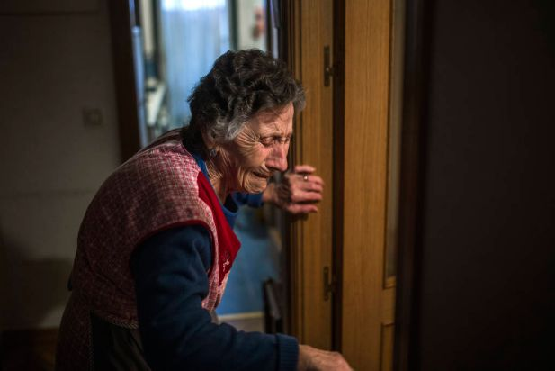 Carmen Martinez Ayudo, 85, cries during her eviction in Madrid, Spain, Friday, Nov. 21, 2014. Carmen Martinez Ayudo, who lives with a pension of euro 630 a month ($ 783) lost her foreclosed apartment to a moneylender after she could not afford to pay her debt and the high interest rates due to her financial situation after her son lost his job. Martinez Ayudo was evicted in spite of housing right activists clashing with the dozens of riot police.
