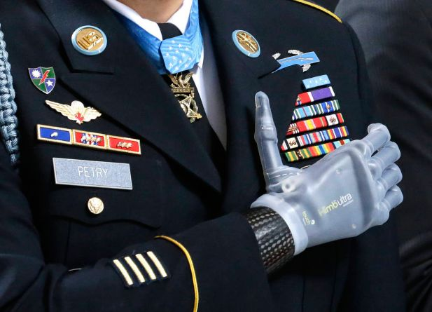 "Medal of Honor recipient Sgt. 1st Class Leroy Petry stands with his prosthetic hand over his heart, wearing his Medal of Honor during the ""Pledge of Allegiance"" at the Capitol in Olympia, Wash. on Wednesday, April 2, 2014, during a ceremony to honor him and other recipients of the Medal of Honor from Washington state. Petry lost his hand in 2008 when an enemy grenade he was throwing away from fellow soldiers detonated while in combat in Afghanistan."