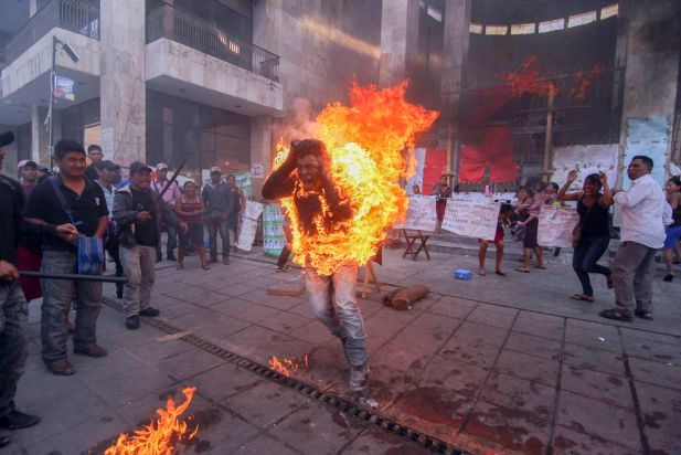 "Farmer Agustin Gomez Perez, 21, runs engulfed in flames after he was lit on fire as a form of protest outside the Chiapas state legislature in Tuxtla Gutierrez, Mexico, Friday, Dec. 5, 2014. Perez was demanding the release of his father, indigenous leader Florentino Gomez Giron, who was arrested last year on charges stemming from a series of demonstrations in 2011 that turned violent. Agustin was taken to a hospital, and his stepmother, Araceli Diaz, said he was ""serious but stable"" condition with second- and third-degree burns."