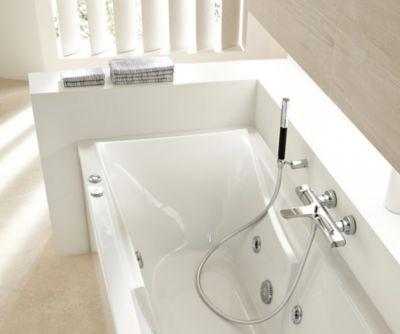 Une salle de bains lumineuse avec un grande baignoire Balnéo et une robinetterie chromée
