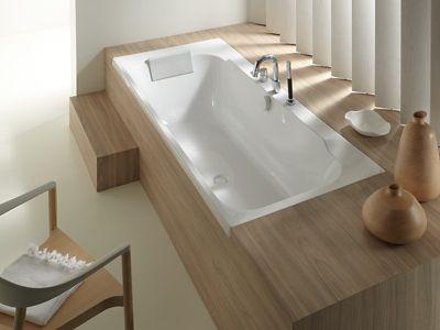 Une baignoire  blanche encastrée dans un tablier de baignoire tout en bois décorée de jarres
