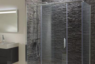 Un espace de douche avec des parois transparentes et un receveur de douche blanc. Des murs en parement de pierre au style industriel.