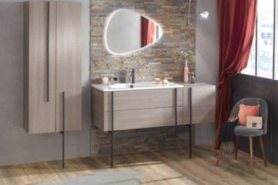 Un meuble sous plan-vasque rose avec une colonne de rangement avec des piétements noirs et un miroir asymétrique aux formes asymétriques avec contour Led pour un esprit vintage