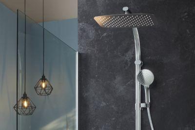 Un espace de douche contenant des WC, une douche ouverte avec paroi fixe et une robinetterie en chrome