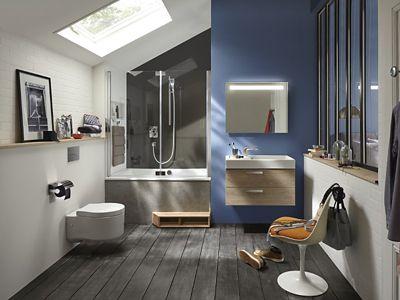 Une grande salle de bains avec une baignoire capsule détenant un tablier assorti au sol en parquet