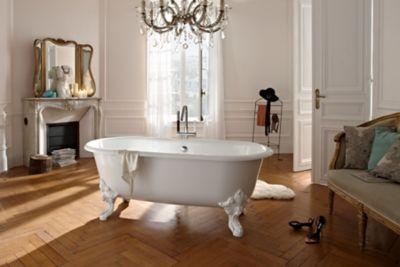 Une salle de bains parisienne au style haussmannien avec une grande baignoire d'époque blanche au milieu de la pièce et du parquet au sol