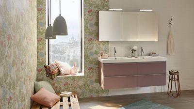 Une salle de bains au style parisien vintage avec un grand meuble rose laqué avec 4 compartiments de rangement, un grand miroir au dessus du plan vasque et un banc en palette de bois
