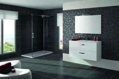 Une grande salle de bains moderne avec de grand carrelages noirs au sol et au mur et de la faïence noire sur un mur. Un grand miroir au dessus d'une plan vasque accompagné de son meuble blanc assorti