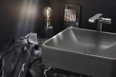 Une vasque gris orage sur un plan de toilette en marque noir avec marbrures blanches et un manteau en cuir posé dessus