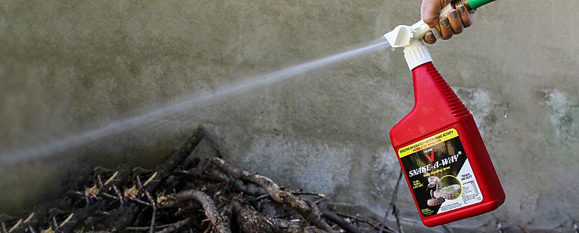 Snake-A-Way Hose End Snake Repellent being sprayed on wood pile