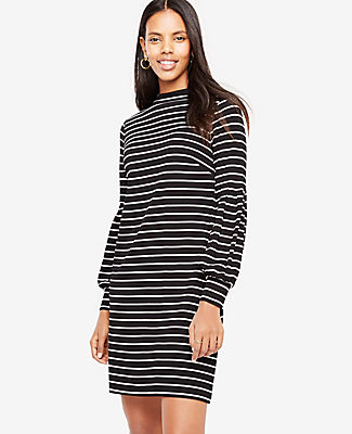 Dressed up (but down for anything), this versatile knit dress goes wherever you're going. Mock neck. Long sleeves with box pleat sleeve seams and shirred cuffs. Exposed metal back zipper. Lined. 21 from natural waist.