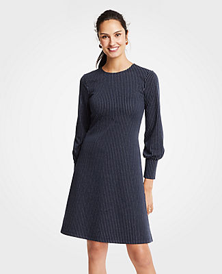 Meet your real-life uniform: this is Luxewear. Every day. Every wear. Rule the day (and night) with our pinstripe dress, highlighted with smartly cuffed sleeves. Jewel neck. Long sleeves with shirred cuffs. Hidden back zipper with hook-and-eye closure.