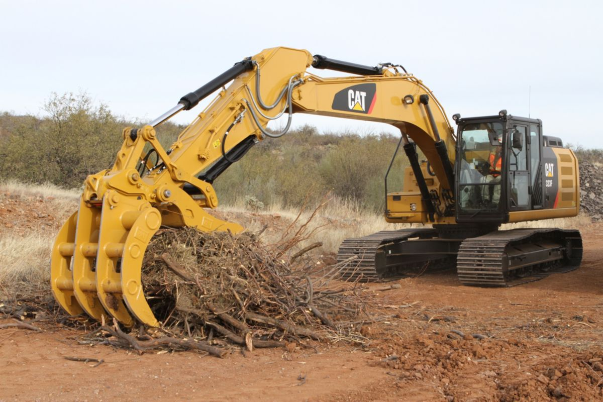Excavator Rake and Pro Series Thumb working together to handle brush.>