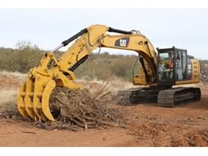 Excavator Rake and Pro Series Thumb working together to handle brush.
