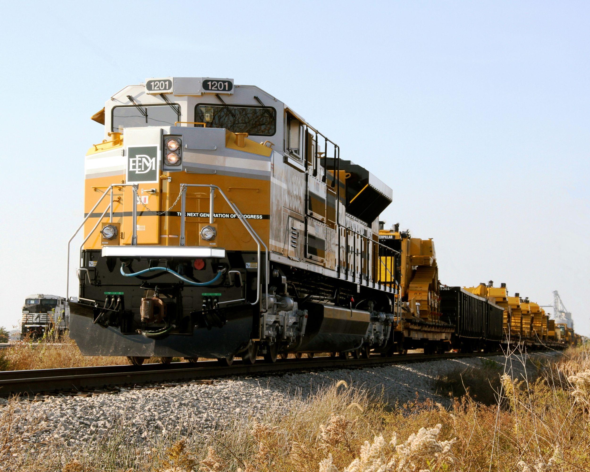 An EMD engine pulls a trainload of Caterpillar dozers.