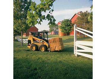 216 skid steer loader at work on a farm.
