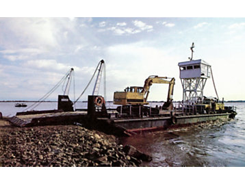Machines being loaded on a boat at a site near the dam.