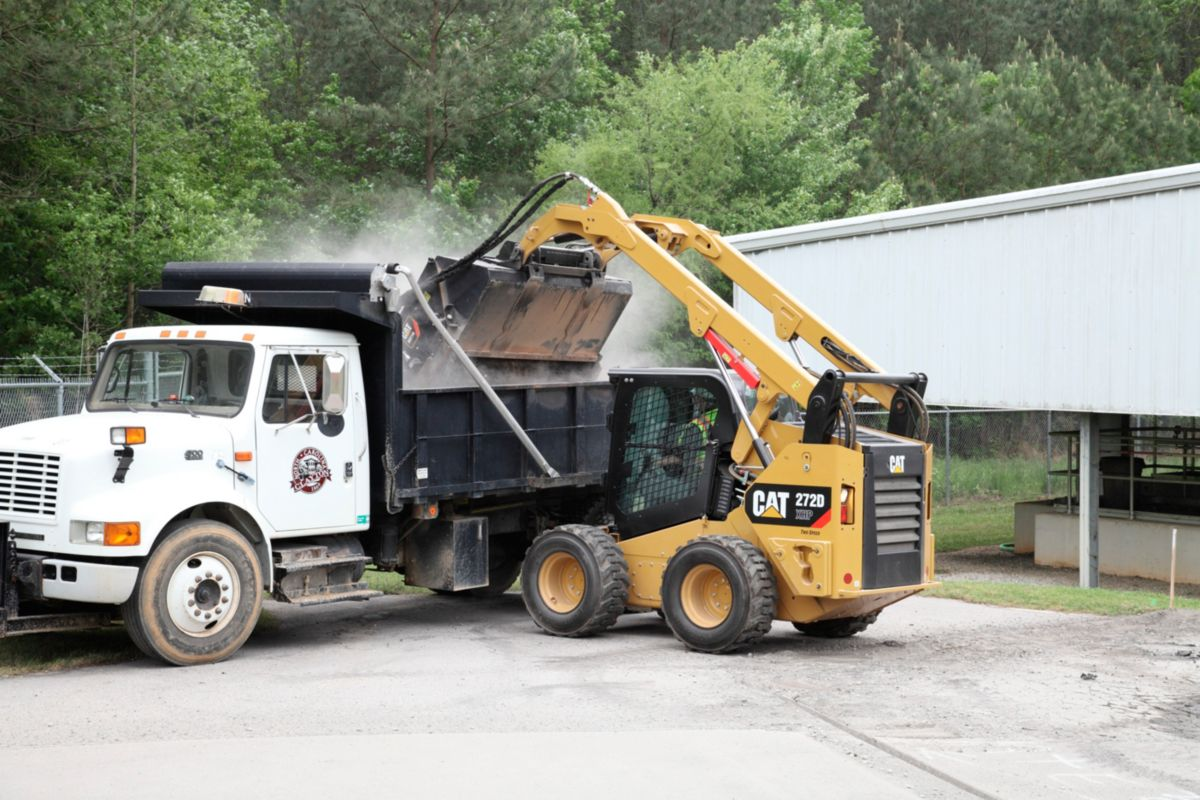 Cat® Utility Broom Dumping Debris into waiting Dump Truck>