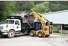 Cat® Utility Broom Dumping Debris into waiting Dump Truck