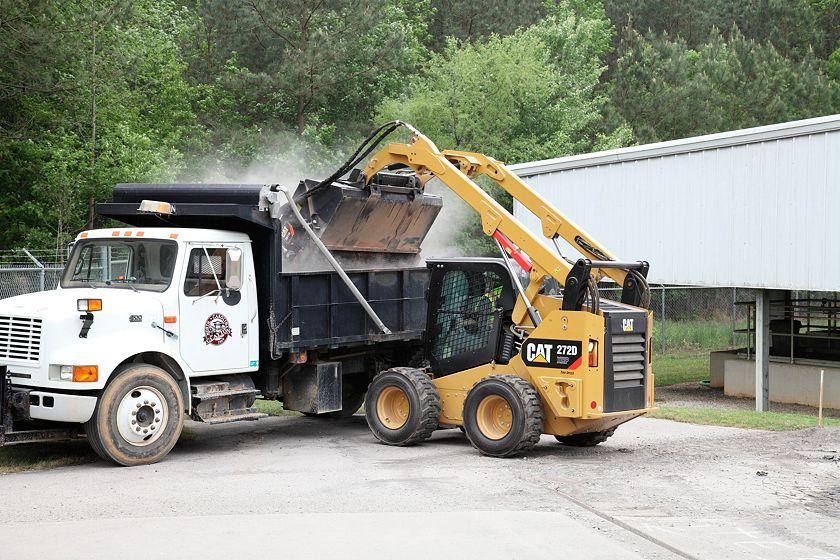 Cat® Utility Broom Dumping Debris into waiting Dump Truck