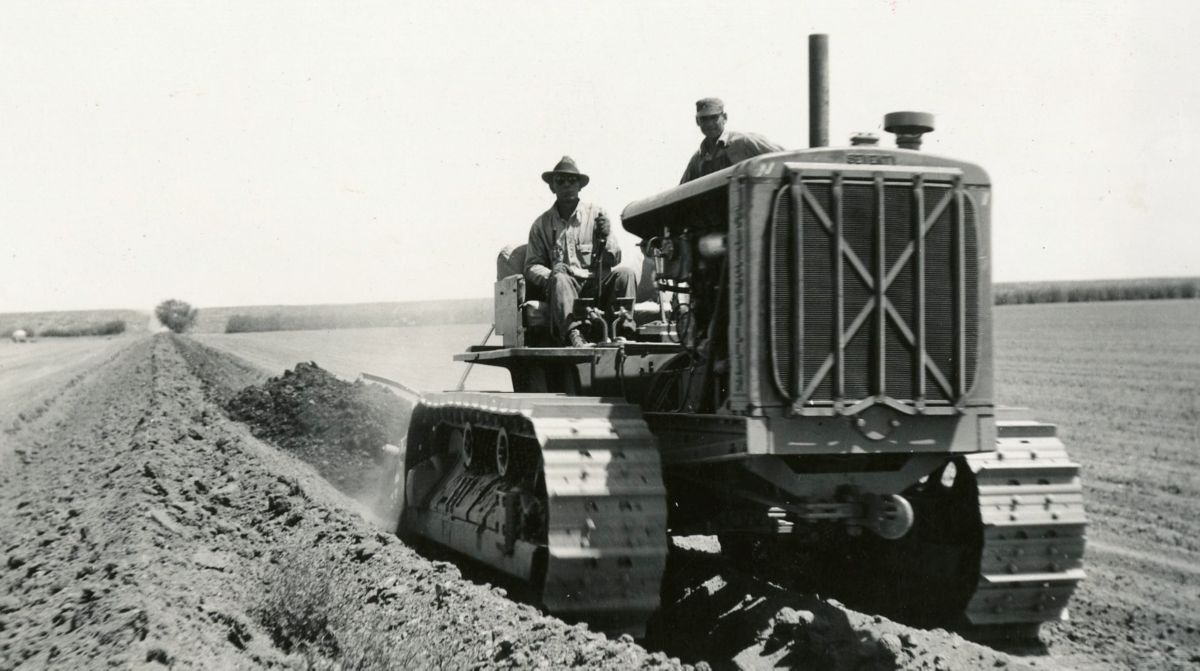 Caterpillar Seventy track-type tractor equipped to burn butane, building an irrigation ditch in Hanford, California.