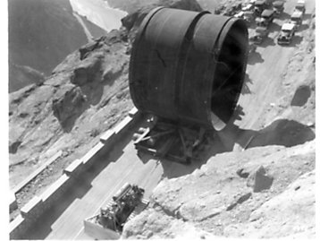 Caterpillar Sixty track-type tractor hauls huge sections of pipe to be used in the construction of Hoover Dam in 1935.