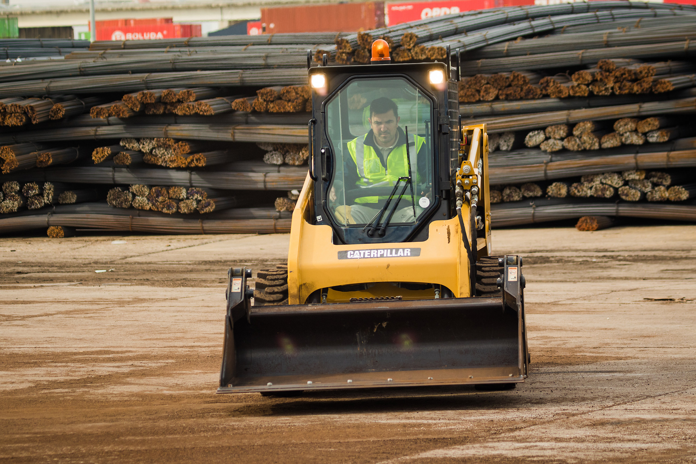 Un cliente utilizando un iPad con la excavadora en marcha en segundo plano