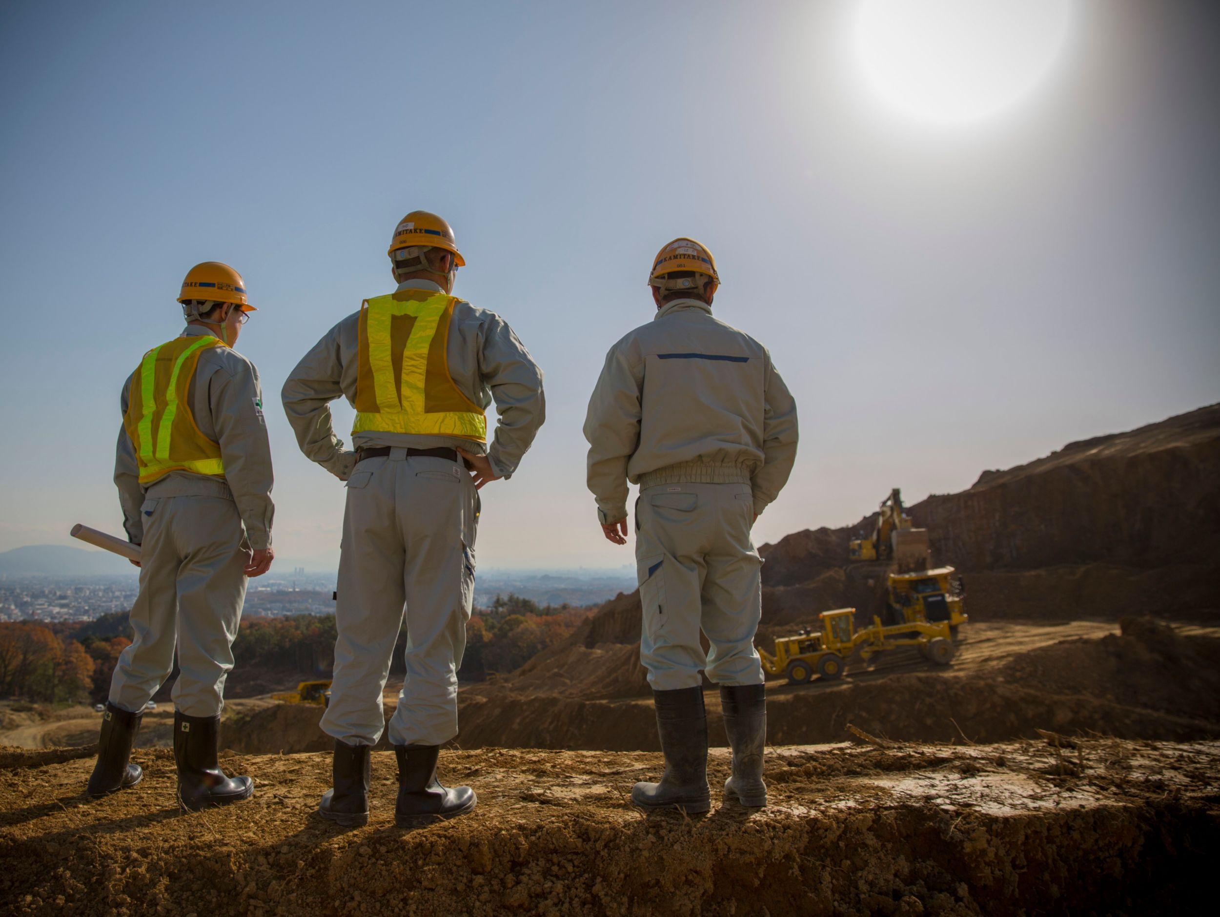 Three men construction gear looking at mining jobsite