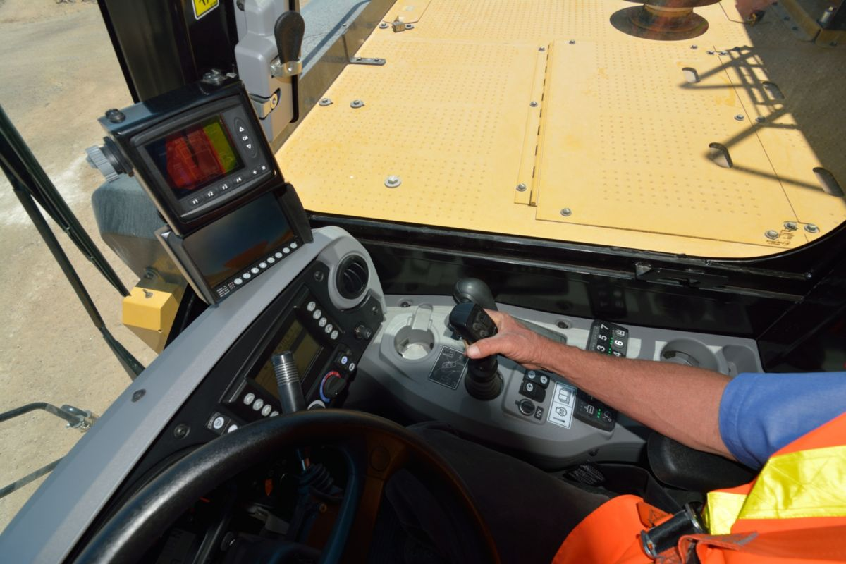 Operator using the Cat Water Delivery System integrated cab controls and electronics in a water truck at the Tuscon Proving Ground (TPG)>